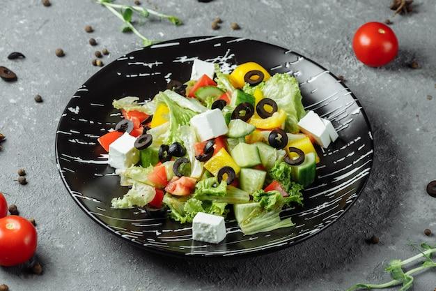 Греческий салат с огурцом, оливками каламата, сыром фета, сочными помидорами черри и свежим базиликом. домашняя еда. концепция вкусной и здоровой вегетарианской еды. вид сверху. скопируйте пространство.