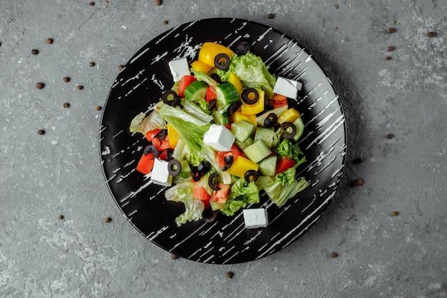Greek salad with cucumeber, kalamata olives, feta cheese, juicy cherry tomatoes and fresh basil