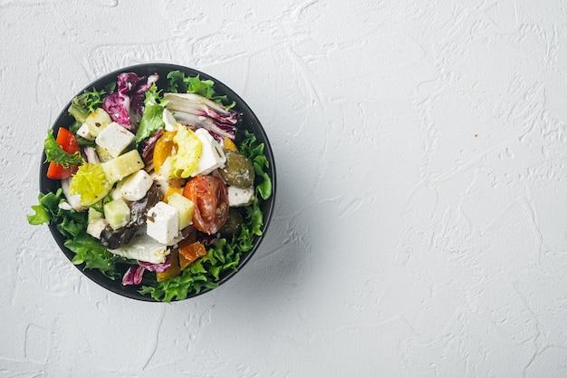 Греческий салат с сыром фета и органическими свежими оливками на белом