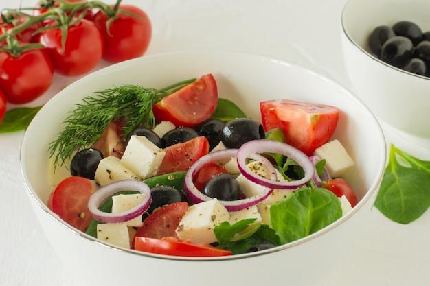 Греческий салат с сыром фета, оливками, сочными помидорами, красным перцем, красным луком, огурцом и листьями салата.