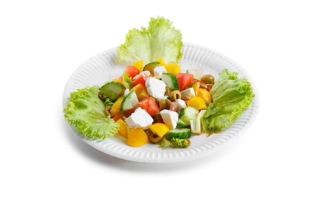 白い背景で隔離の白いプレートにフェタチーズ、チェリートマト、コショウ、キュウリのギリシャ風サラダ