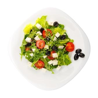 Греческий салат с фетой, помидорами черри, перцем и огурцом на белой тарелке