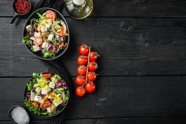 검은 나무 테이블 배경에 신선한 야채, 페타 치즈, 올리브 칼라마티가 있는 그리스 샐러드, 텍스트 복사 공간이 있는 평면도