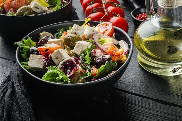 Греческий салат со свежими овощами, сыром фета и оливками каламати, на черном деревянном столе
