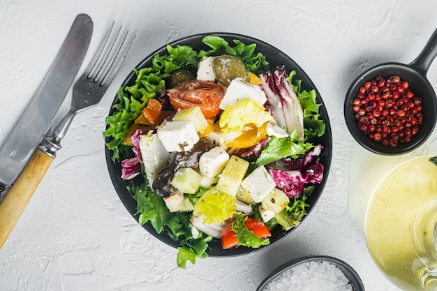 Греческий салат со свежими овощами, сыром фета и оливками каламати, на белом фоне, плоский вид сверху