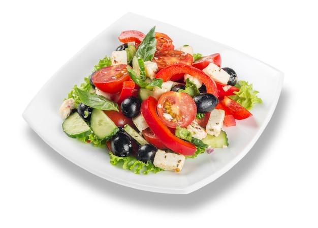 Греческий салат со свежими овощами на белом фоне