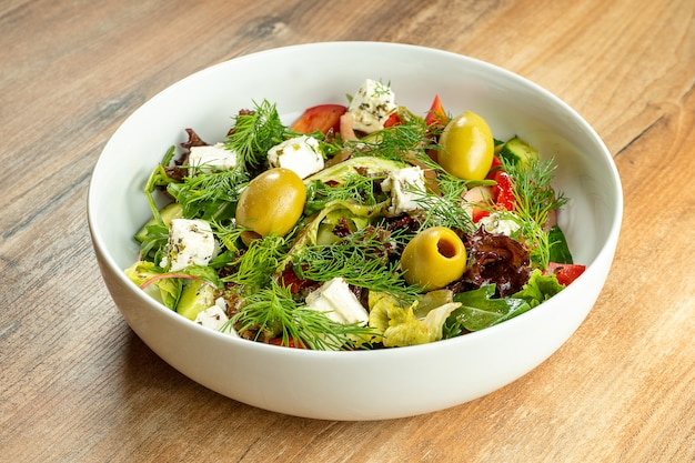 Greek salad with green olives, feta cheese, tomatoes, avocado and arugula in white bowl on wooden. fresh, healthy vegan salad for lunch. food photo for menu or recipe