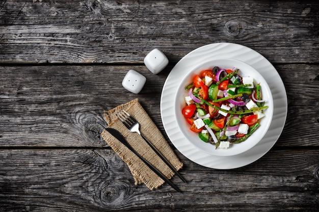 グリルしたアスパラガス、チェリートマト、きゅうり、ブラックオリーブ、オリーブオイルを添えた赤玉ねぎのリング、木製のテーブルにカトラリーを添えたプレートにフェタチーズを添えたギリシャ風サラダ、上面図、コピースペース