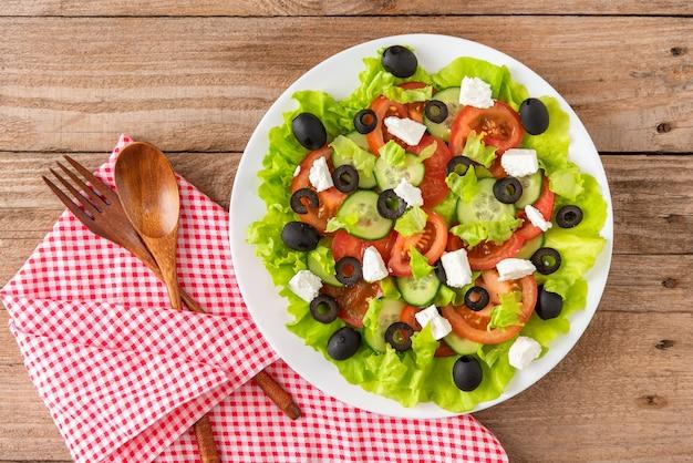 Греческий салат с оливками и сыром фета к столу. вид сверху.