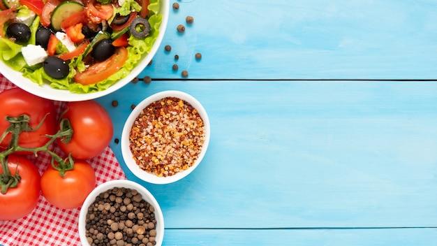 木製の青いテーブルにオリーブ、フェタチーズ、新鮮な野菜を添えたギリシャ風サラダ。