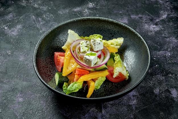 黒い表面に黒いボウルにトマト、タマネギ、コショウ、フェタチーズのギリシャ風サラダ。ダイエット食品