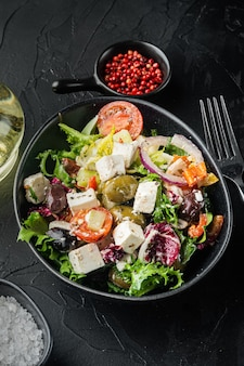 검은 배경에 토마토, 후추, 올리브, 페타 치즈를 곁들인 그리스 샐러드