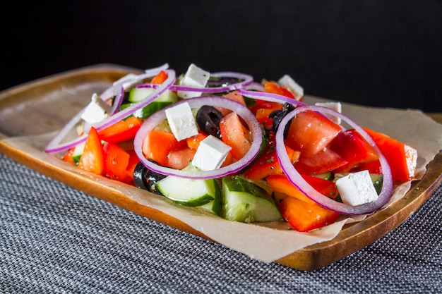 Greek salad in a wooden plate