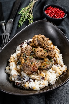 Greek style lamb stew in a tomato, with rice.  black background.