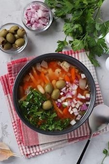 Греческий томатный суп с овощами, оливками и белой фасолью в темной миске на серой поверхности. вид сверху. вертикальный формат