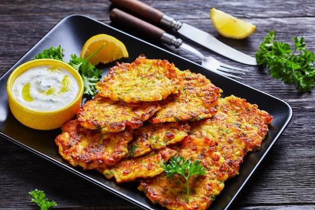 그리스 tzatziki 소스와 파삭 파삭 한 양파 latkes는 칼 붙이, 클로즈업으로 어두운 나무 테이블에 레몬과 신선한 파슬리와 함께 검은 접시에 제공