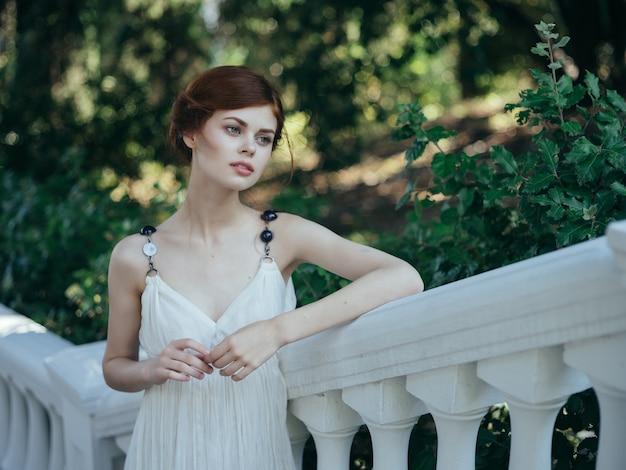 公園の自然ファッションの夏の白いドレスを着たギリシャの女性。高品質の写真