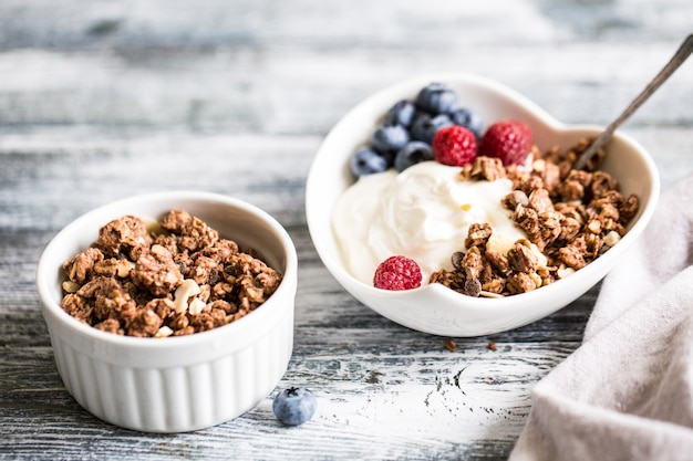 Greek yogurt, blueberries, raspberries and granola in a white bowl