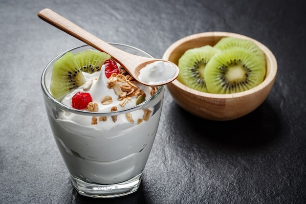 Greek yogurt in a glass with kiwi on black stone slab