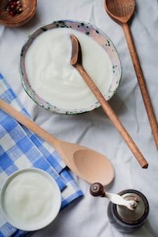Греческий йогурт в керамической тарелке с деревянными ложками