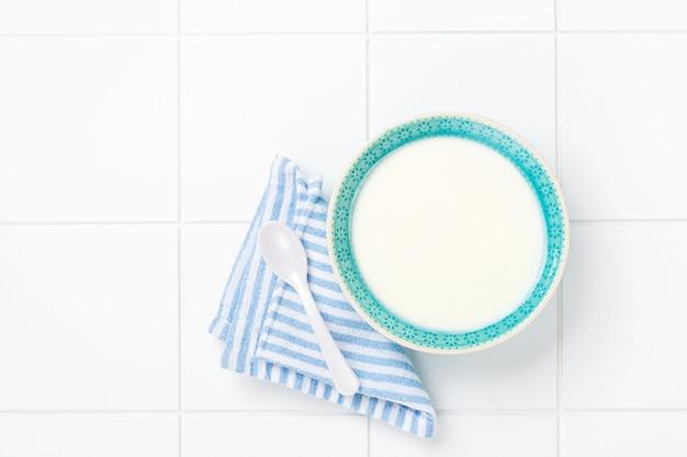Греческий йогурт в голубой шаре, льняной салфетке и деревянной ложке на белом столе. вид сверху