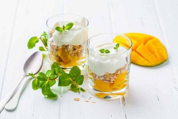 Greek yogurt mango granola parfait in a glass on white wood