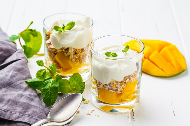 Greek yogurt mango granola parfait in a glass on white wooden background.