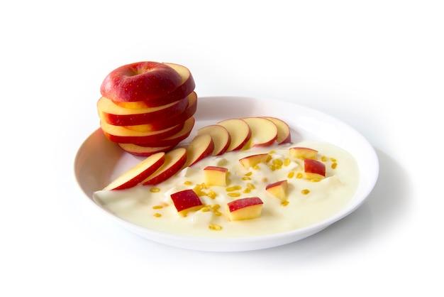 Greek yogurt original flavour with fresh slice red apple on the white plate