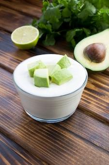 Греческий йогурт с авокадо на деревянном столе