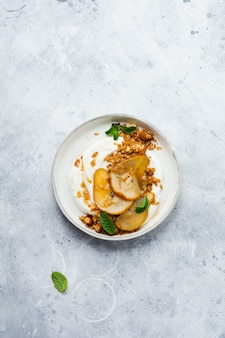 Greek yogurt with caramelized pear, granola, nuts and melted sugar for a wholesome breakfast on a gray ceramic plate. rustic style. top view.