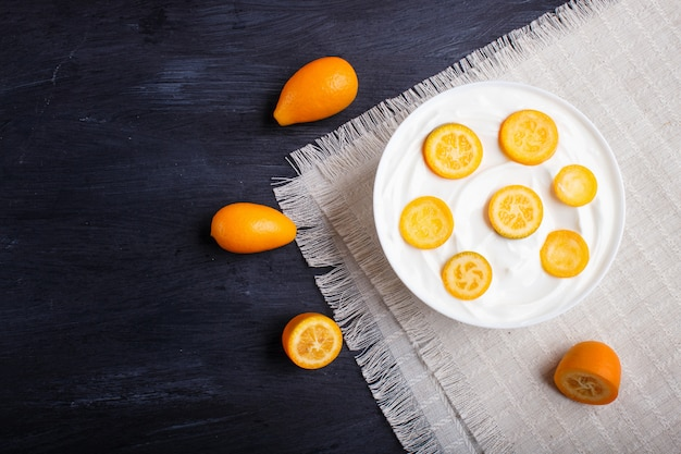 Greek yogurt with kumquat pieces in a white plate on a black wooden background