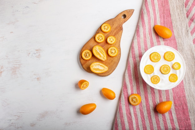 Greek yogurt with kumquat pieces in a white plate on a white wooden background
