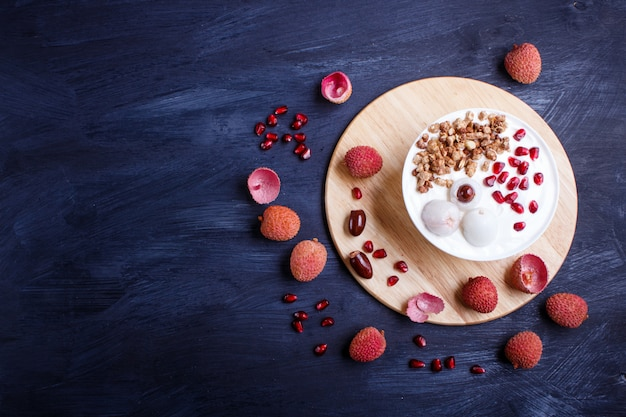 Greek yogurt with lychee, pomegranate seeds and granola in a white plate on black wood