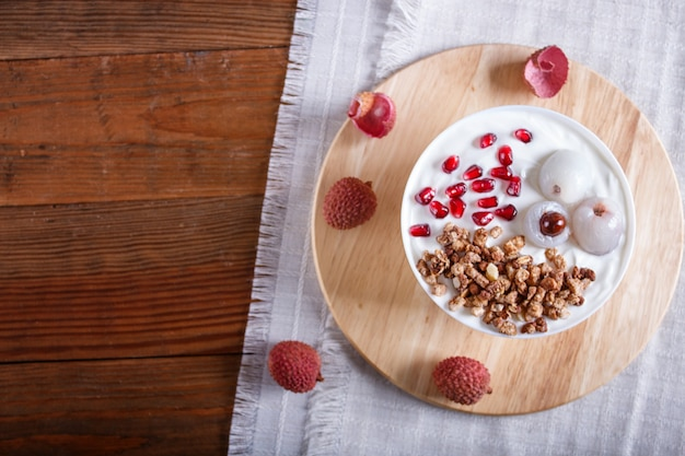 Greek yogurt with lychee, pomegranate seeds and granola in a white plate on a brown wooden background