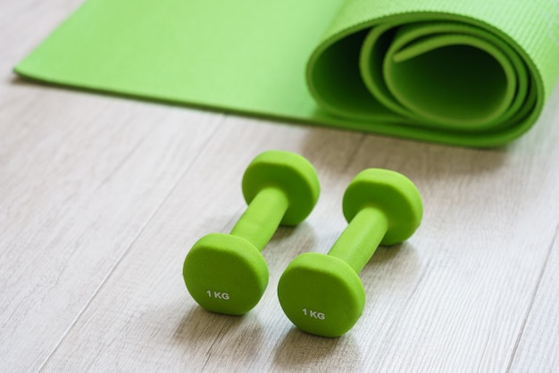 Green 1 kg dumbbells and exercise mat on the light wooden floor equipment for physical workout