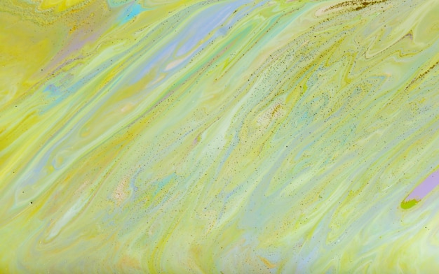 Green abstract painting with golden glitter. abstract liquid background