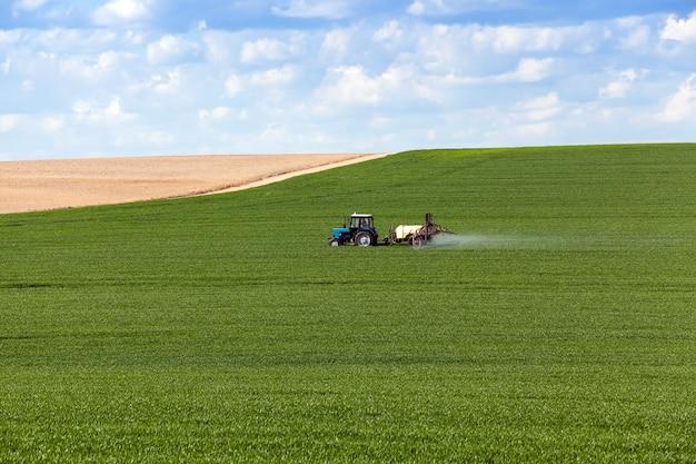 トラクターで処理される穀物のある緑の農地