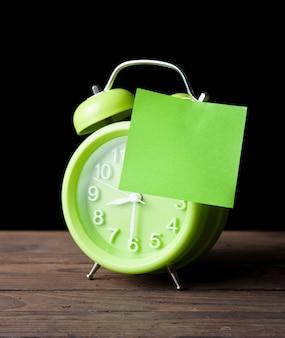 緑色の目覚まし時計、白い背景、暗い背景に隔離されたテキストスペースの付箋紙