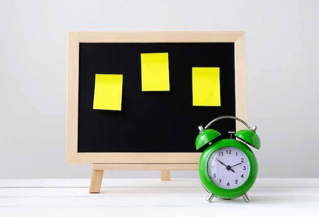 Green alarm clock and empty blackboard with sticky note pad on white table