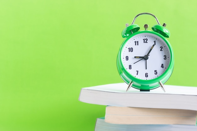 The green alarm clock is located on the stack of books with green background