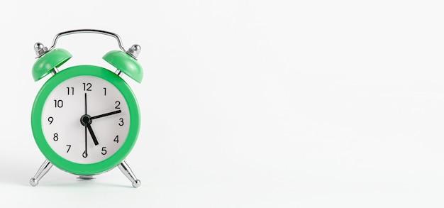 白い壁に緑の目覚まし時計。時間と締め切りのコンセプト