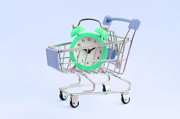 Green alarm clock in supermarket trolley on blue