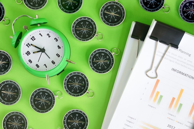 Green alarm clock surrounded by a compass with stack of financial documents on green background