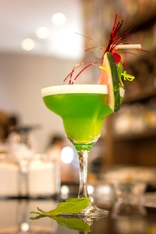 Green alcoholic cocktail with mint in a margarita glass on a bar counter
