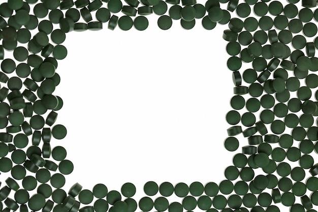 Green algae spirulina in tablets. frame background