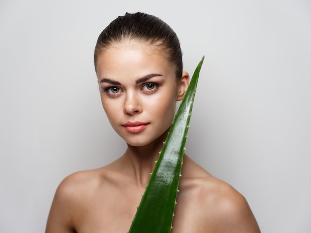 Green aloe leaf on shoulder nude women with fashionable hairstyle