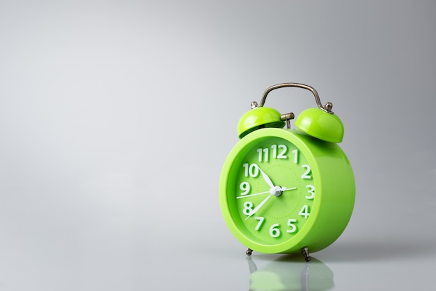 Green analog alarm clock gray background with light and shadow, copy space.
