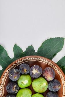 세라믹 접시와 흰색 배경에 녹색과 검은 색 무화과. 고품질 사진