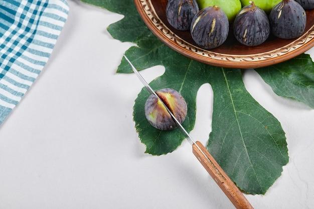 칼과 잎을 가진 세라믹 접시에 녹색과 검은 색 무화과. 고품질 사진