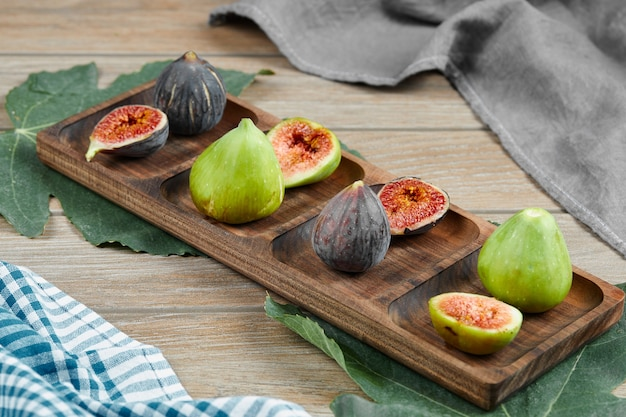 葉とテーブルクロスと木製の大皿に緑と黒のイチジク。高品質の写真